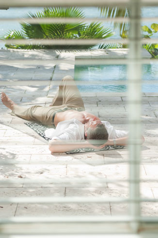 man laying by pool seen through blinds