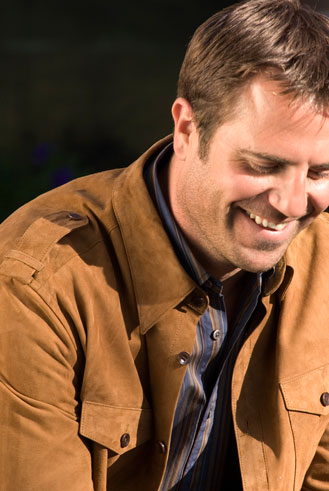 close up of man smiling in suede jacket