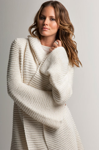 woman in white cable knit sweater coat
